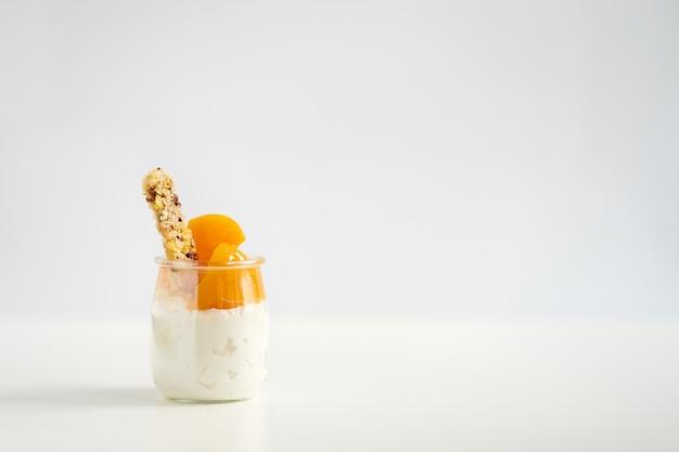Glas joghurt oder quark mit müsli und dosen aprikosen