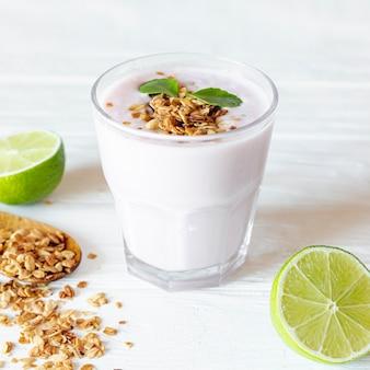 Glas joghurt und halb geschnittene limette
