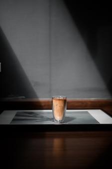 Glas kaffee auf dem tisch und graue wand