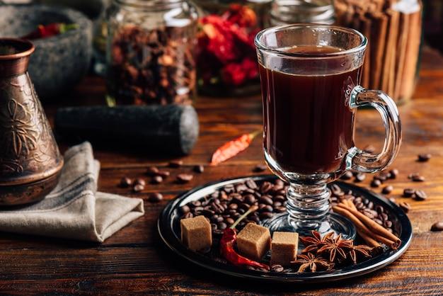 Glas kaffee mit bohnen, raffiniertem zucker, sternanis, zimtstange und chilischote.