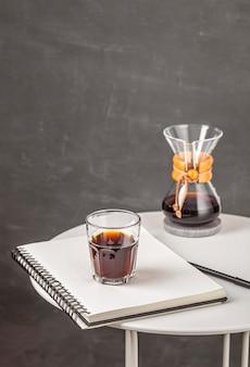Glas kaffee mit chemex auf dem tisch