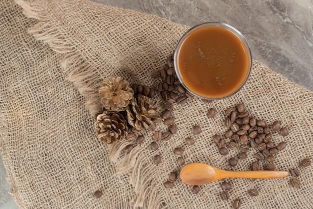 Glas kaffee mit kaffeebohnen und löffel auf sackleinen