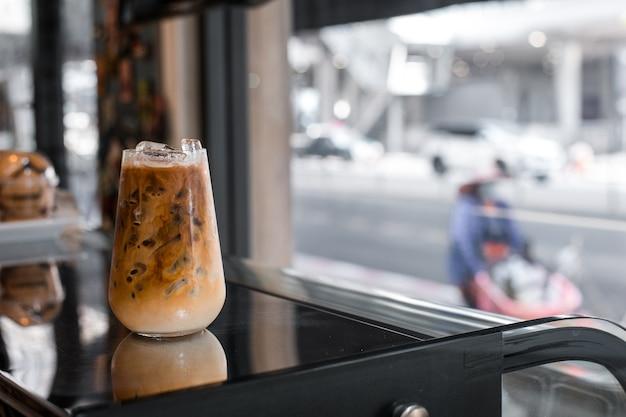 Glas kaffee mit milch auf einer weißen leinwand
