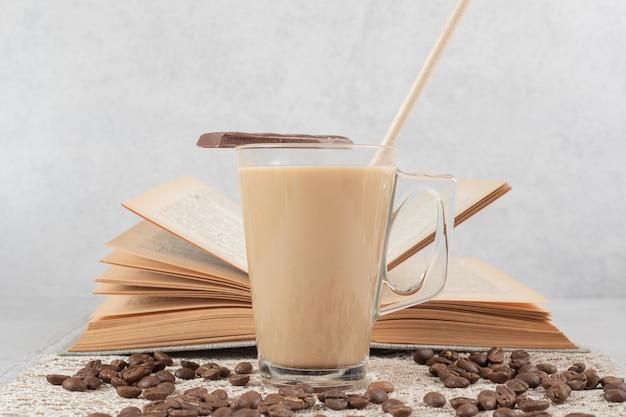 Glas kaffee mit schokolade, buch und kaffeebohnen auf sackleinen
