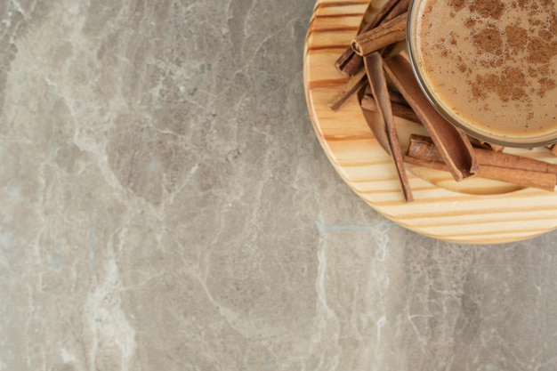 Glas kaffee mit zimt auf holzbrett