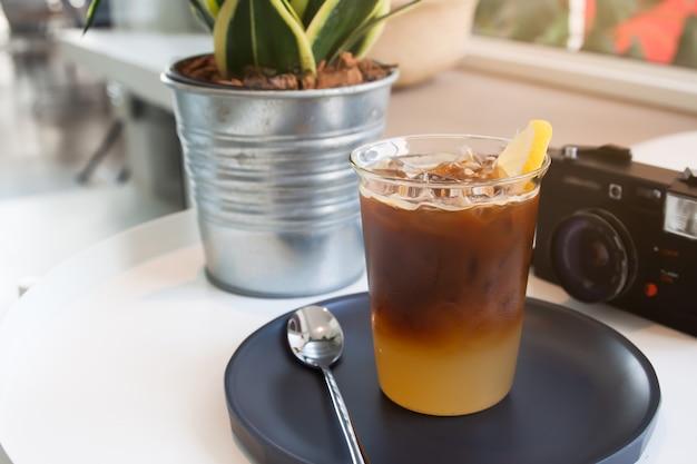 Glas kaffee und kamera auf dem tisch im café