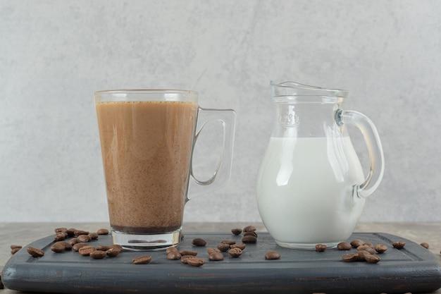 Glas kaffee und milch auf dunklem teller