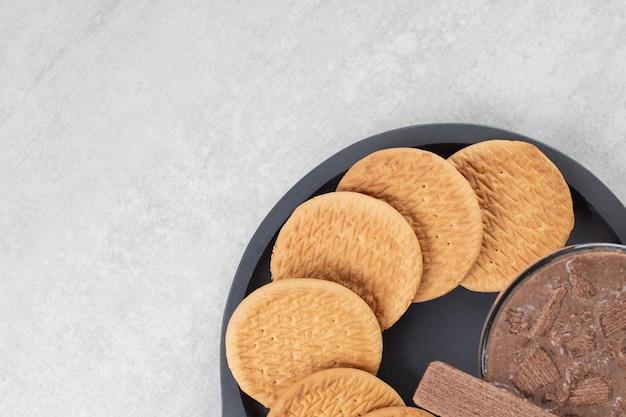Glas kaffee und verschiedene kekse auf dunklem brett