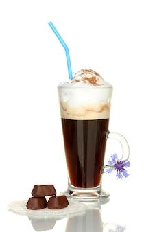 Glas kaffeecocktail mit schokoladenbonbons auf deckchen und blume auf weiß