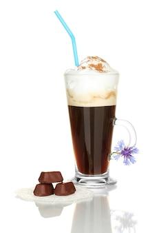 Glas kaffeecocktail mit schokoladenbonbons auf deckchen und blume lokalisiert auf weiß