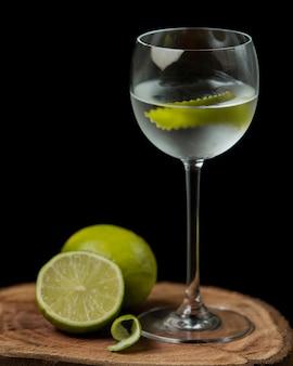 Glas kalkwasser mit kalkschale auf hölzernem umhüllungsbrett