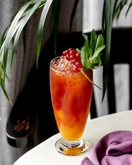 Glas kalter cocktail mit roter johannisbeere garniert