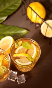 Glas kalter erfrischungstee mit eis und zitronenfrucht.