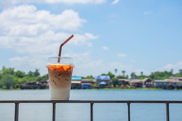 Glas kalter espressokaffee auf dem eisernen balkon mit blick auf den fluss und das haus.