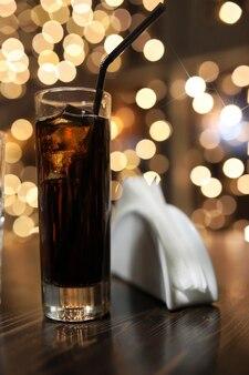 Glas kaltes alkoholgetränk mit eis auf dem tisch