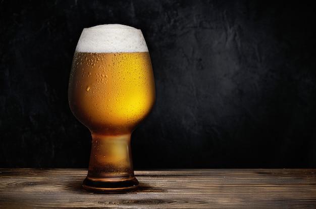 Glas kaltes bier auf einem rustikalen holztisch