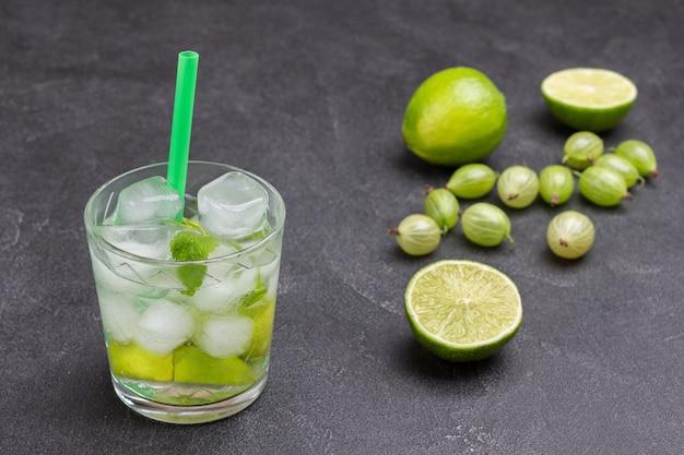 Glas kaltes getränk mit limette, minze und eis. stroh im glas. limettenscheiben und stachelbeeren auf dem tisch. schwarzer hintergrund. ansicht von oben