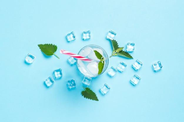 Glas kaltes und erfrischendes wasser mit eis und minze auf einem blauen hintergrund. eiswürfel. konzept von heißem sommer, alkohol, kühlendem getränk, durstlöschung, bar. flache lage, draufsicht
