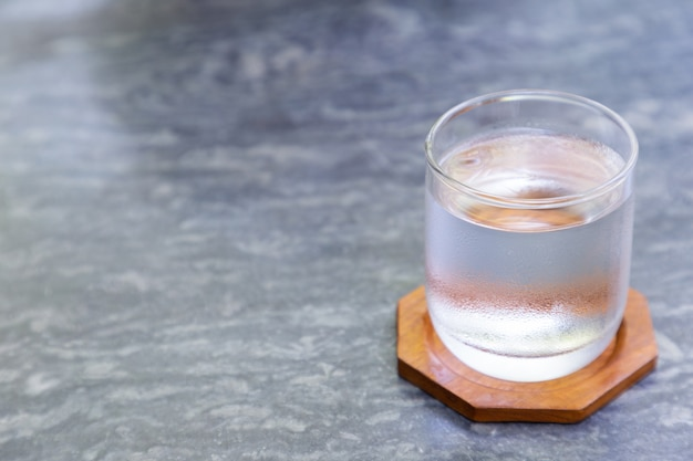 Glas kaltes wasser mit hölzernem untersetzer auf grauer steintabelle in der kaffeestube.