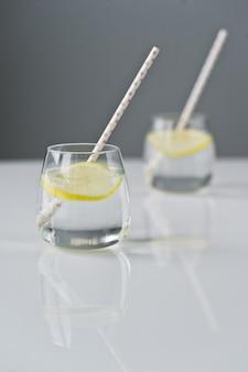 Glas klares wasser mit zitrone und stroh.