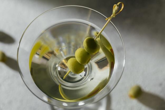 Glas klassischer trockener martini-cocktail mit oliven auf einer grauen steinoberfläche.