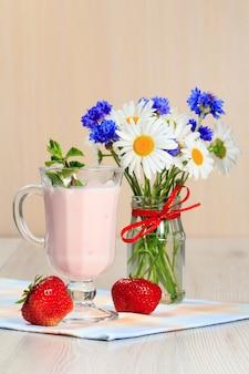 Glas köstlicher joghurt mit minze und frischen erdbeeren, kamille und kornblumen in vase auf einem holztisch mit serviette Premium Fotos