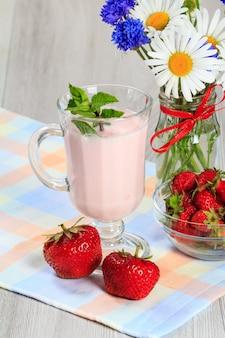 Glas köstlicher joghurt mit minze und frischen erdbeeren, kamille und kornblumen in vase auf einem holztisch mit serviette