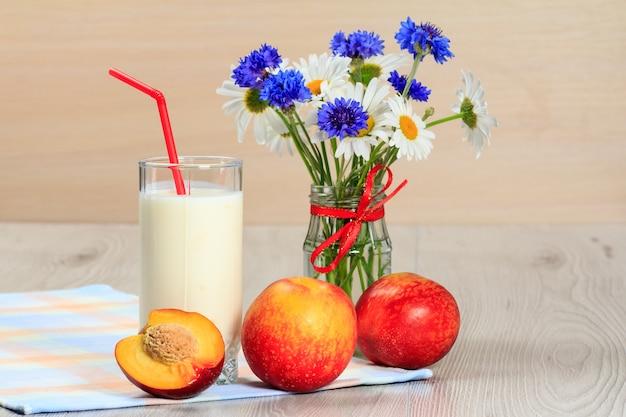 Glas köstlicher joghurt mit minze und frischer nektarine, kamille und kornblumen in vase auf einem holztisch mit serviette Premium Fotos