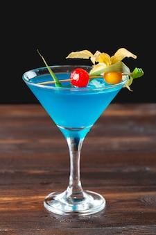 Glas köstliches alkoholisches cocktail auf dunkelheit