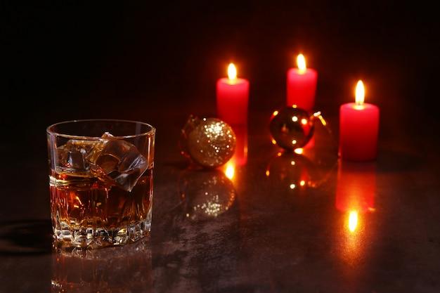 Glas kognak oder whisky, rote kerzen und bunter ball auf hölzernem