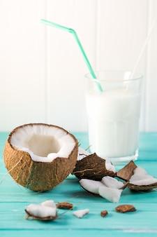 Glas kokosmilch auf blauem holztisch