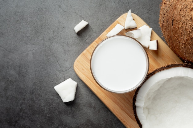 Glas kokosmilch auf holzschneidebrett setzen