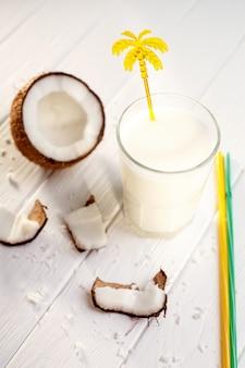 Glas kokosmilch auf weißem holztisch