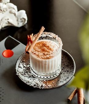 Glas kokosnusscocktail mit ingwerstreuseln garniert