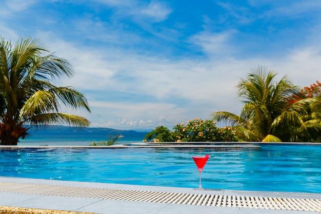 Glas kosmopolitischer cocktail mit kirsche am rand des infinity-pools im hotel