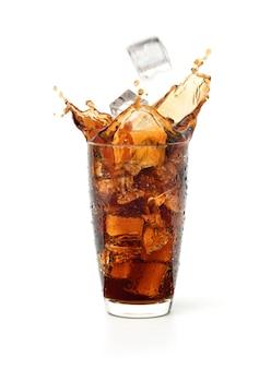 Glas kühles cola-spritzen mit eis, das isoliert auf weißem hintergrund fällt.