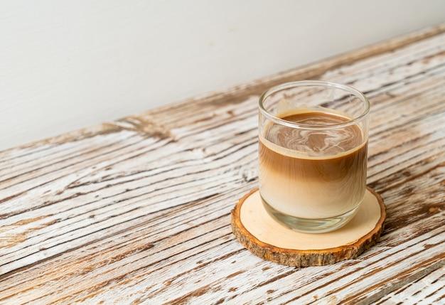 Glas latte kaffee, kaffee mit milch auf holzscheibe