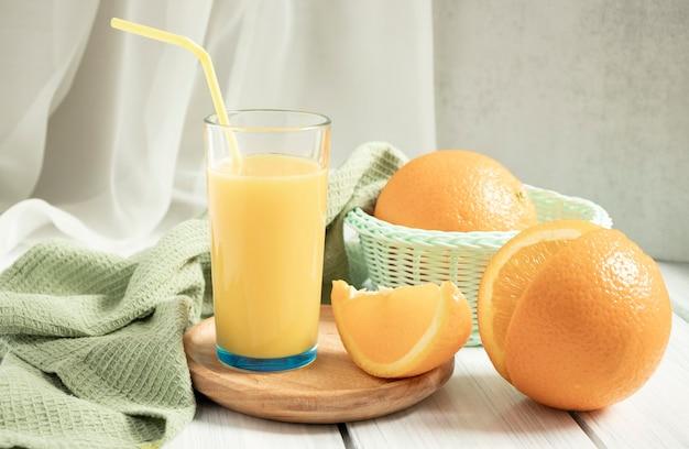 Glas leckeren orangensaft und reife orangenscheiben gesunde ernährung detox getränk vitamin hellgrau hintergrund draufsicht