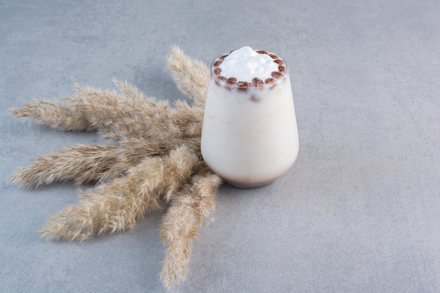 Glas leckerer eiskaffee mit milch auf steintisch.