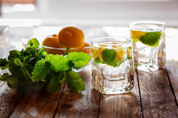 Glas limonade mit frischer zitrone und minze auf hölzernem hintergrund