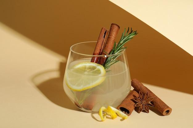 Glas limonade mit zimt und rosmarin auf beigem hintergrund