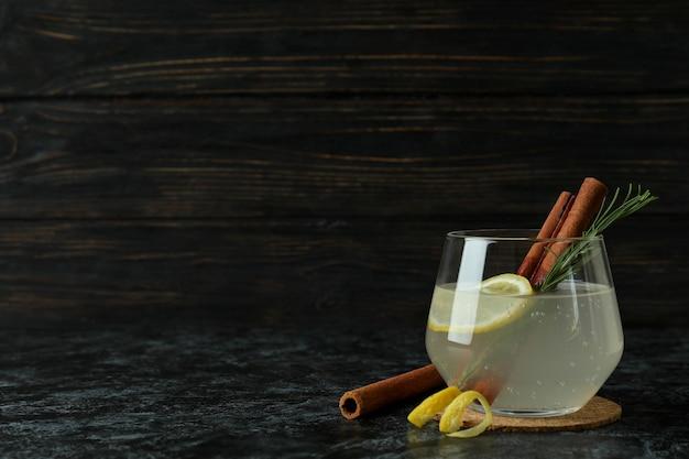 Glas limonade mit zimt und rosmarin auf schwarzem rauchtisch