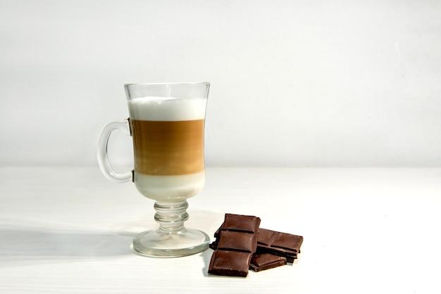 Glas macchiato latte mit dunkler schokolade.