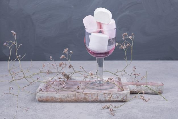 Glas marshmallows auf holzbrett mit pflanze. hochwertiges foto