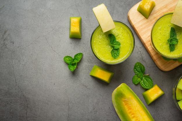 Glas melonensaft auf dunklen boden stellen