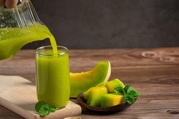 Glas melonensaft auf holzboden gestellt