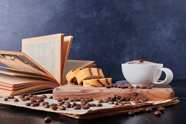 Glas milch mit kaffeepulver und rollcake-scheiben.