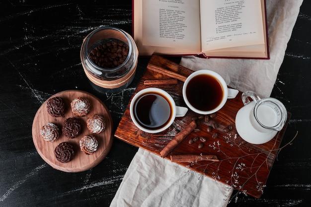 Glas milch mit kaffeetassen und keksen