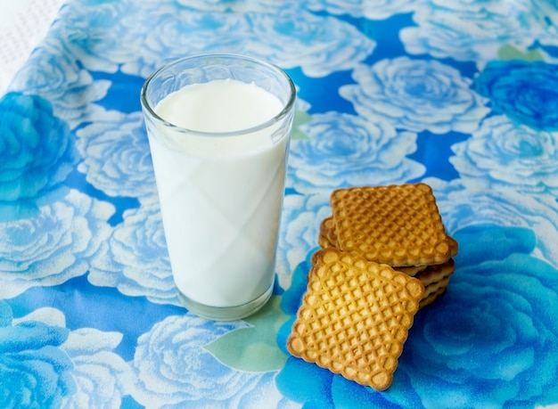 Glas milch mit plätzchen auf blauem hintergrund