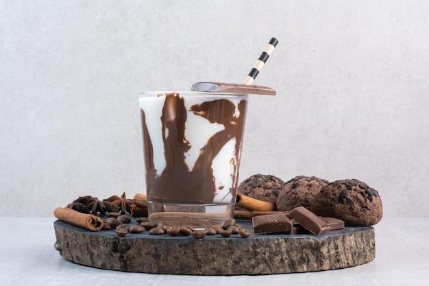 Glas milch mit strohhalm, schokolade und keksen auf holzstück. foto in hoher qualität